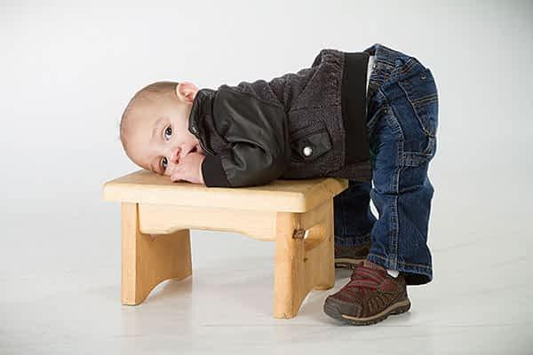 boy laying on a stool